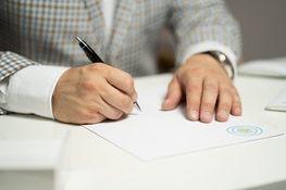 ręce piszą długopisem na kartce papieru