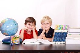 chłopczyki za biurkiem, książki, zeszyty, kolorowe kredki