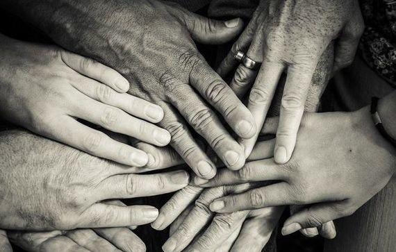 Grafika przedstawiająca splecione dłonie