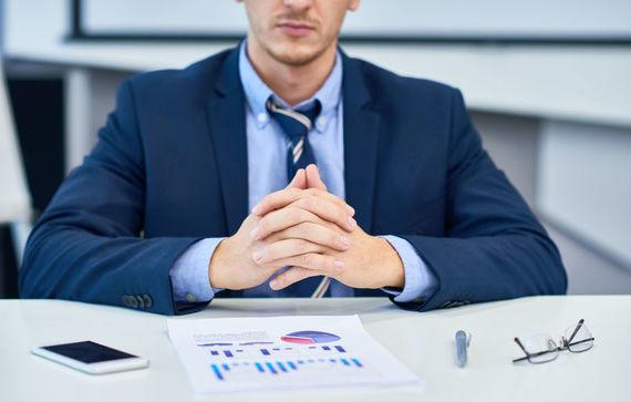Grafika przedstawia pana siedziącego przy biurku