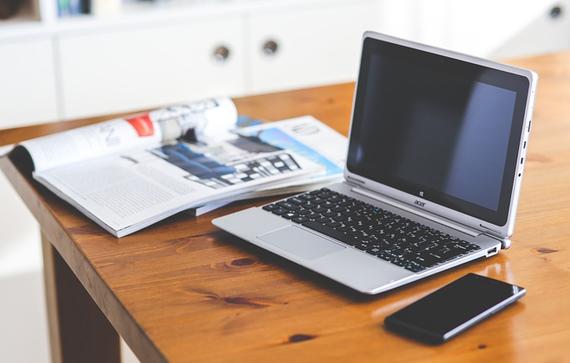 Grafika przedstawiająca biurko, laptopa oraz dokumenty i telefon