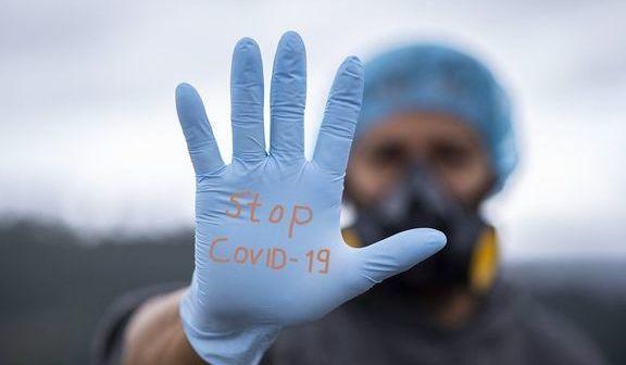 """mężczyzna w masce i rękawiczkach, na rękawiczce napis """"stop COVID-19"""""""