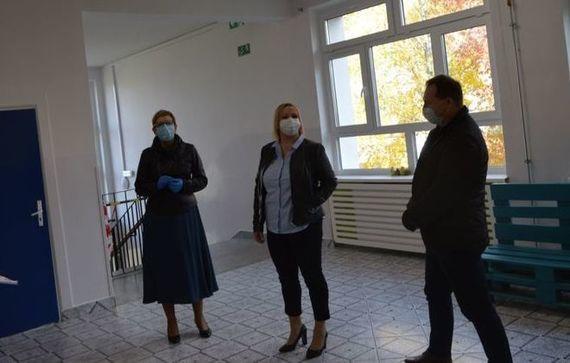 Trzy osoby w maseczkach podczas odbierania budynku