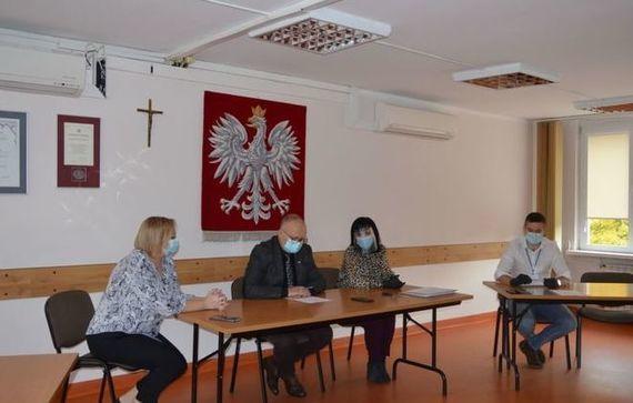 Zdjęcie czterech osób siedzących w ławkach