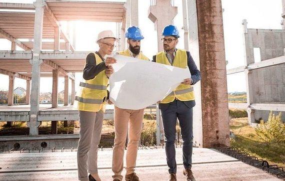 Trzech architektów w kaskach przy planie na tle budowy