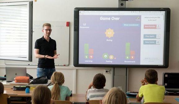 Klasa z uczniami i nauczycielem stojącym przy interaktywnej tablicy.