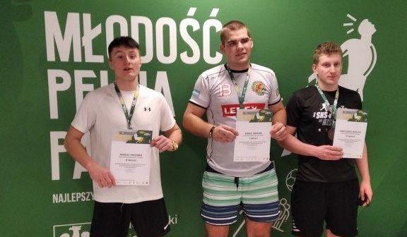 Trzy osoby z dyplomami i medalami