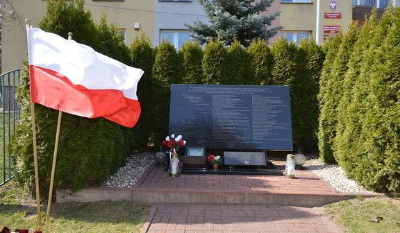 Pomnik w postaci płyty ozdobiony kwiatami i zniczami. Obok powiewają dwie flagi Polski. Całość otoczona szeregiem tui.