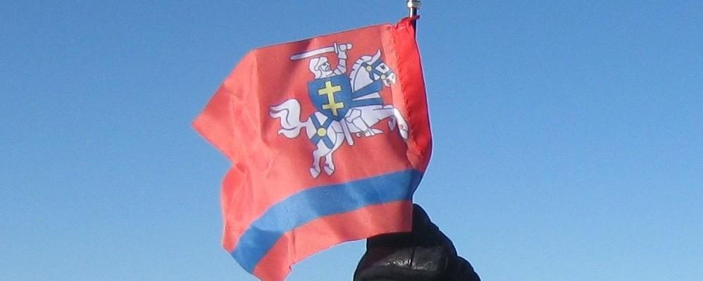 """Wystawa """"Mont Blanc - wspomnienia z wyprawy"""" z flagą Powiatu Puławskiego w tle"""