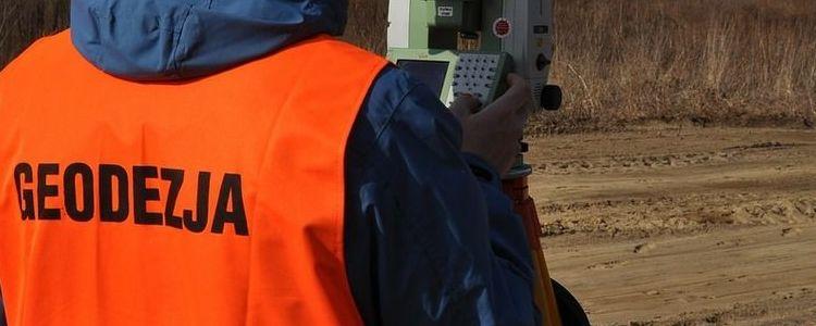 Geodezja, pomarańczowa kamizelka, aparatura pomiarowa