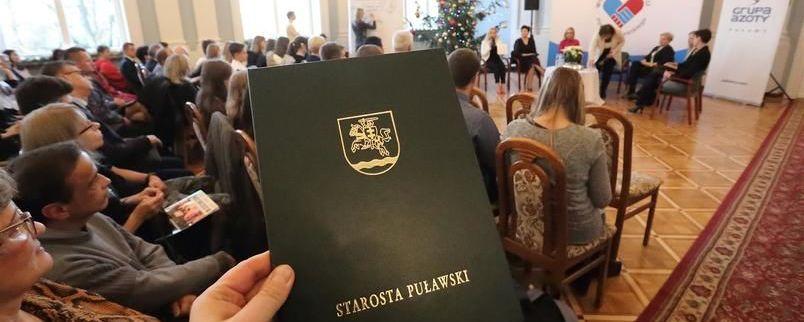 Powiatowe święto wolontariatu - sala Pompejańska w tle. Na pierwszym miejscu herb powiatu z napisem starosta puławski.