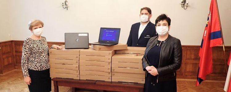 Starosta Danuta Smaga, kierownik wydziału edukacji Małgorzata Noskowska i sekretarz powiatu Waldemar Orkiszewski prezentują zakupione laptopy do nauki online.
