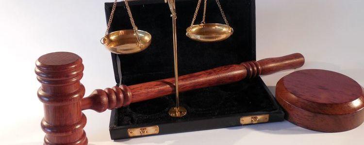 Symbolika wymiaru sprawiedliwości - młotek sędziowski i waga szalowa.