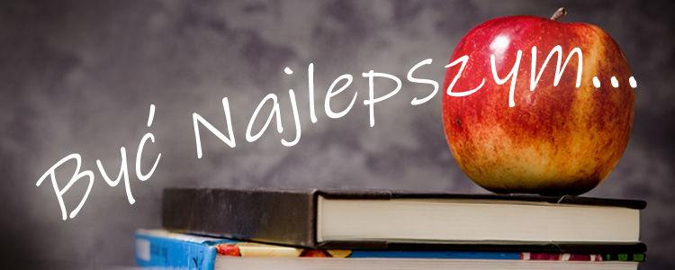 """Napis """"Być najlepszym"""". W tle jabłko i książki."""