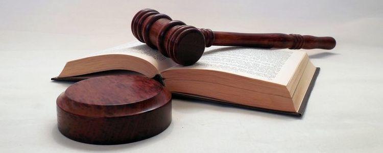 Symbolika wymiaru sprawiedliwości - młotek sędziowski na otwartej księdze.