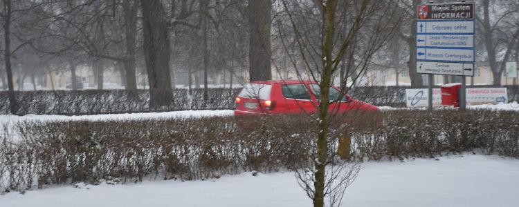 Zamieć śnieżna na ulicy, w tle czerwone auto i znaki miejskiego systemu informacji