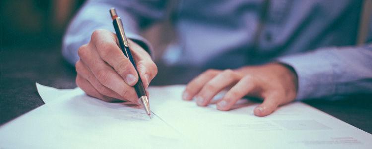 Zdjęcie przedstawia ręce składające podpis na dokumentach.