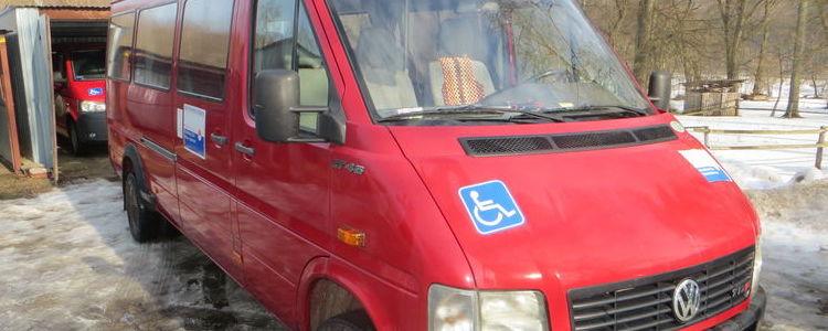 czerwony bus dla osób niepełnosprawnych, w tle garaż, zima