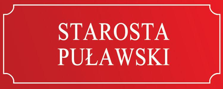 """Tabliczka , czerwone tło białe litery """"Starosta Puławski"""""""
