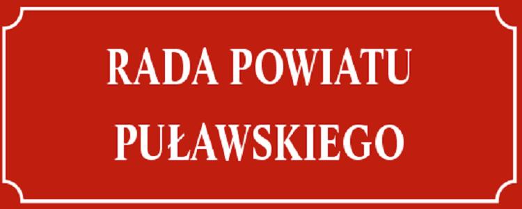 Tablica czerwone tło i napis białymi literami Rada Powiatu Puławskiego