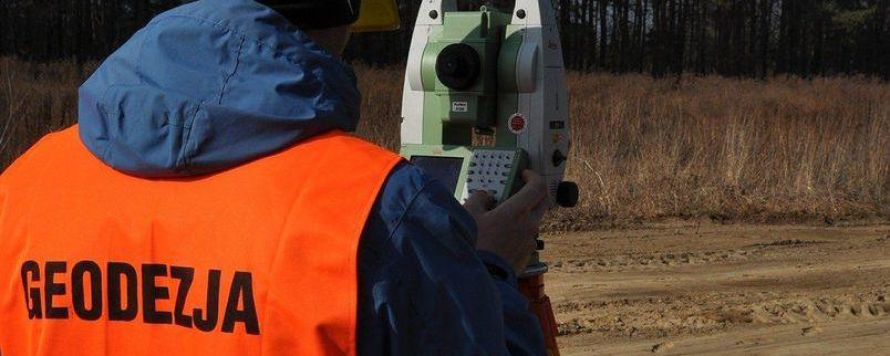 mężczyzna w pomarańczowej kamizelce robiący pomiary geodezyjne w terenie