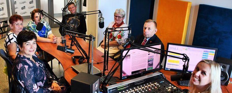 Wnętrze studia nagrań Radio Impuls, ludzie przy stole z mikrofonami