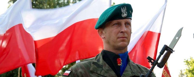 żołnierz, w tle flagi