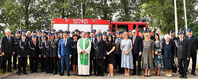 Strażacy z OSP Włostowice z gośćmi. W tle samochód strażacki.