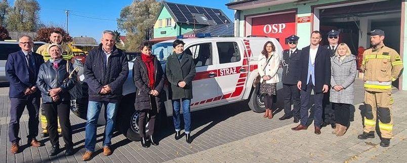 Przekazanie wozu strażackiego, ludzie przed remizą OSP z samochodem