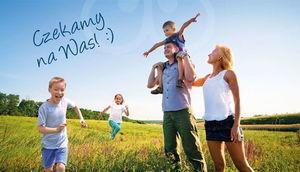 Kawałek plakatu uśmiechnięta rodzina i napis Czekamy na Was!