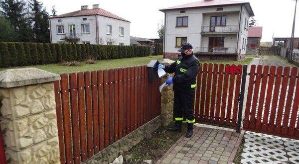 Strażak wrzuca ulotke do skrzynki