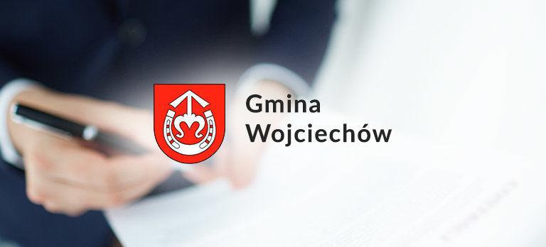 Grafika ogólna- herb gminy Wojciechów na tle osób podających sobie ręce