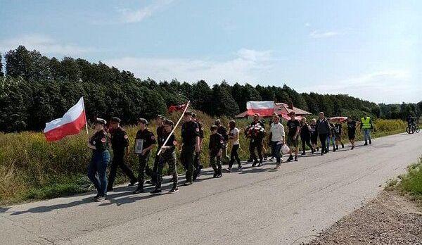 Przemarsz- grupa ludzi z flagami na drodze
