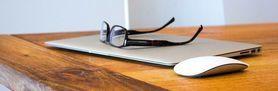 Grafika przedstawia laptopa, okulary oraz myszkę leżące na strole
