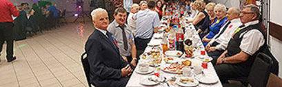 Mieszkańcy przy stołach z jedzeniem
