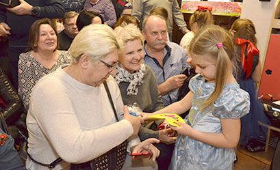 Dziewczynka wręcza babci prezent w tle grupa osób
