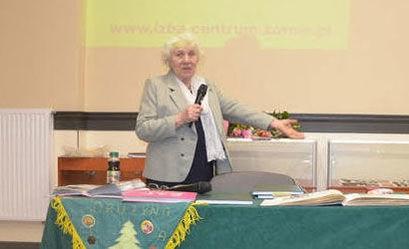 Kobieta przy mikrofonie, w tle prezentacja