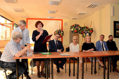 Na zdjęciu grupa osób  przy stole
