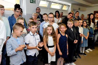 Grupa dzieci i dorosłych stojących w korytarzu