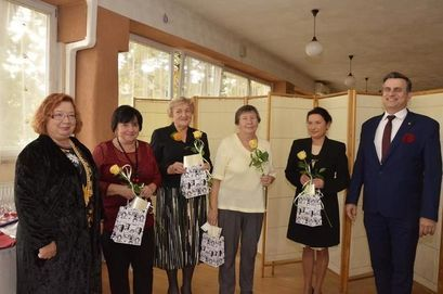 Grupa nauczycieli z kwiatami