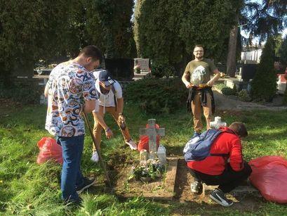 Uczniowie sprzątający groby