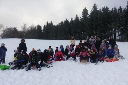 Dzieci i dorosli na śniegu z sankami