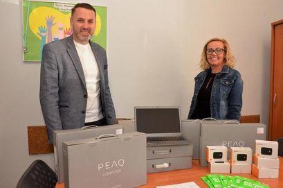 Dwie uśmiechnięte osoby przy komputerach