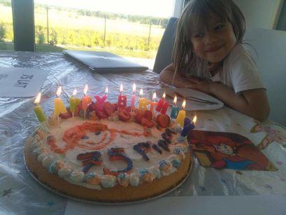 Tort ze świeczkami i uśmiechnięta dziewczynka