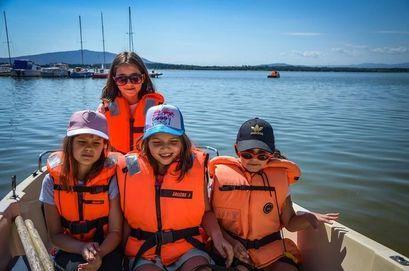 Czworo dzieci na łódce w trakcie pływania po zalewie Mietkowskim