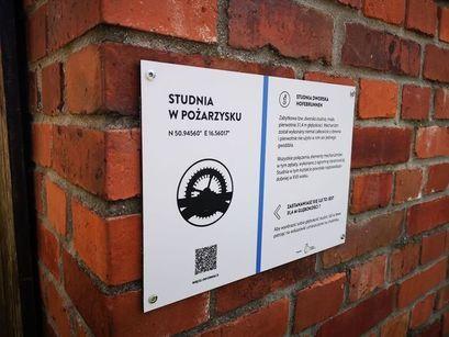 Tablica informacyjna umieszczona na ścianie zabytkowej studni w Pożarzysku