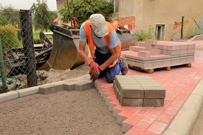 Pracownik układający kostkę betonową podczas remontu chodnika w Wierzbnej.
