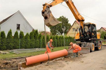 Dwóch robotników układa rurę kanalizacyjną przy wspomaganiu koparki podczas robót przy modernizacji kanalizacji przy ul. Słowiańskiej w Żarowie.