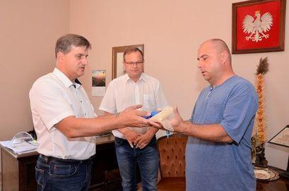 Burmistrz Leszek Michalak i burmistrz Świebodzic Paweł Ozga przekazujący zabytkowy pałasz na ręce Bogdana Muchy z Żarowskiej Izby Historycznej.