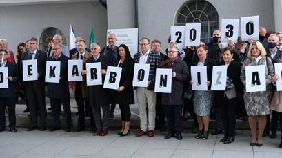 Przedstawiciele samorządów trzymający litery składające się na hasło: Dekarbonizacja 2030